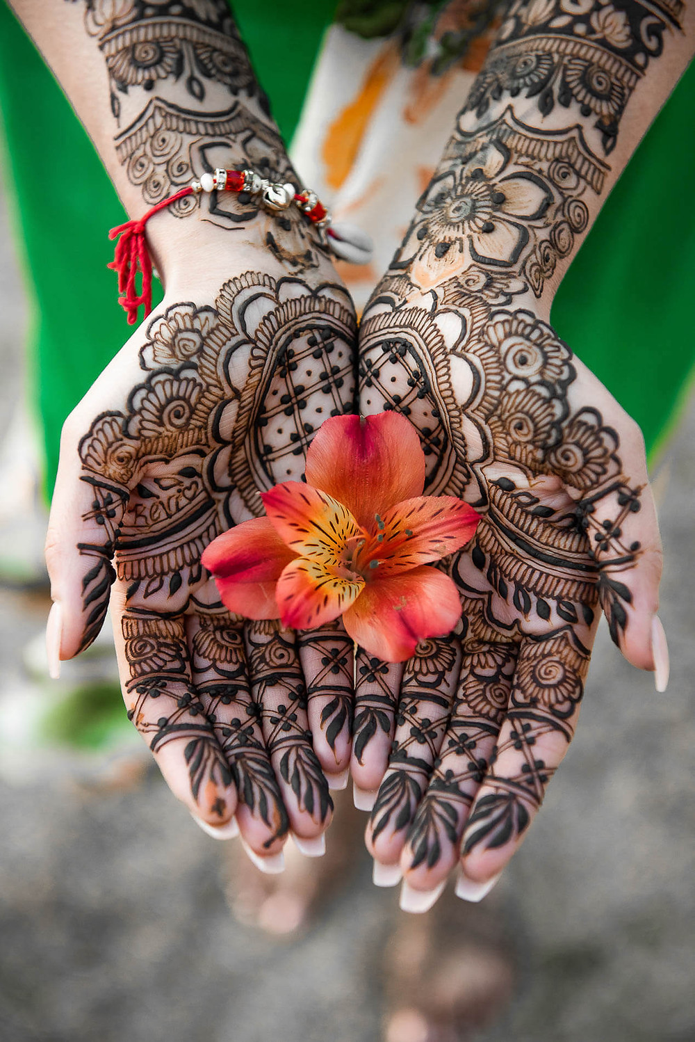 close up of open palms with henna design and lily in the middle
