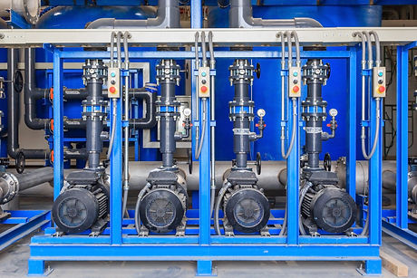 Large industrial water treatment and boiler room.jpg Shiny steel metal pipes and blue pumps and valv