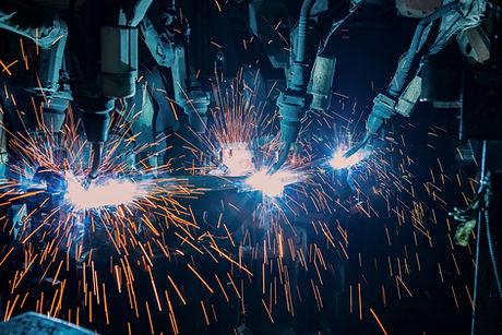 Team robots welding in automotive industrial factory
