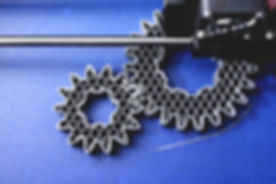 FDM 3D-printer manufacturing spur gears from silver-gray filament on blue print tape - top view on o