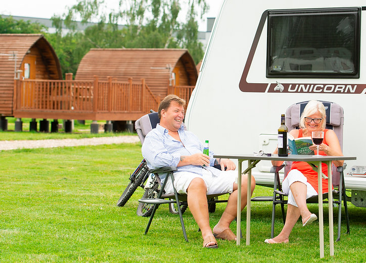 Holiday makers relaxing outside of a caravan