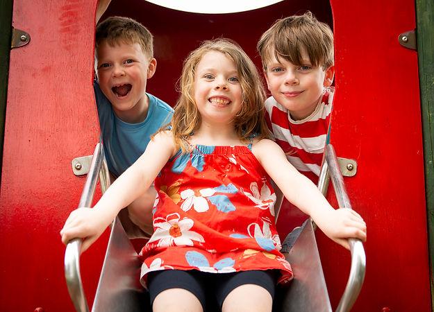 Chilren play on slide in campsite playground
