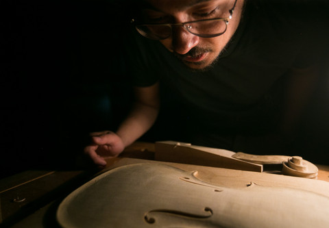 Luthier Jackson Chase inspects an unfinished violin on Thursday, May 2, 2019, at Yakima Maker Space in Yakima, Wash. Chase specializes in handmade violins.
