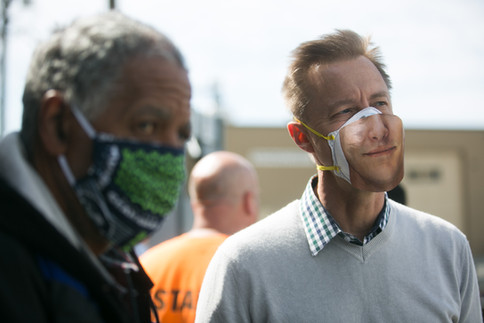 In an effort to bring up spirits, Union Gospel Mission Executive Director Mike Johnson, right, sports a cutout of a face on his medical mask Tuesday, April 7, 2020, at the Yakima Union Gospel Mission in Yakima, Wash.