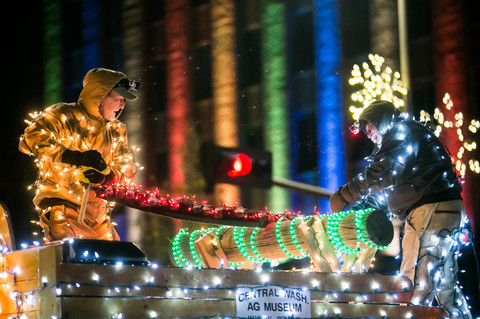 Two Central Washington Agricultural Museum lumberjacks saw a log lit with Christmas lights during the 19th Annual Christmas Lighted Parade on Yakima Avenue in downtown Yakima, Wash. on Sunday, Dec. 2, 2018.