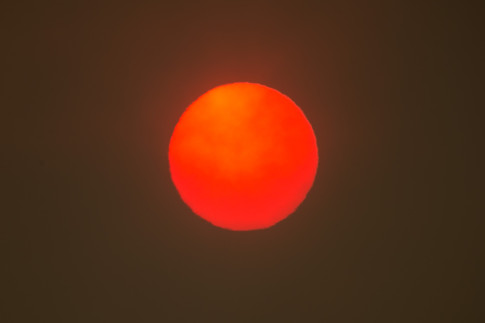 As billows of smoke fill the sky, a red-orange toned sun is seen as a wildfire burns in the Evans Canyon area in Wenas, Wash., on Monday, Aug. 31, 2020.