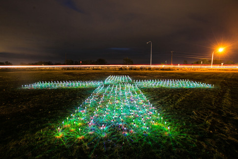A series of lights in the shape of a positive symbol change colors as they shine on the north side of the Yakama Nation Cultural Center lawn Friday, Nov. 6, 2020, in Toppenish, Wash. The lights represent the lives affected by COVID-19 on the Yakama Reservation.