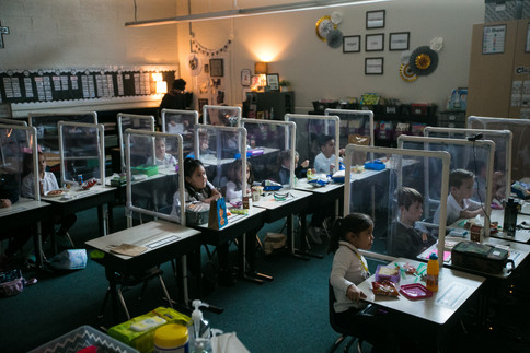 Students in Kathy Wangler's first grade class eat lunch at their desks with protective barriers Wednesday, Oct. 28, 2020, at St. Joseph Marquette Catholic School in Yakima, Wash.