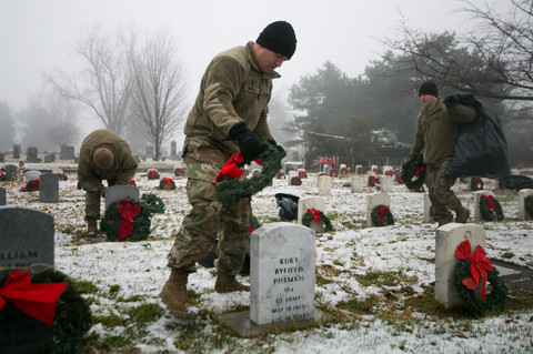 U.S. Army National Guard's Eric Abhold, center, places a wreath on a veteran's gravestone Thursday, Dec. 12, 2019, at Tahoma Cemetery in Yakima, Wash.