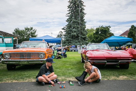 Tommy Bolen, 9, left and Henry Bolen, 7, play with car toys next to their father's 1964 Ford Falcon Sprint, left, and their grandfather's 1965 factory fuel injected Chevrolet Corvette at the 45th annual Vintiques Northwest Nationals Friday, Aug. 2, 2019, at the State Fair Park in Yakima, Wash.