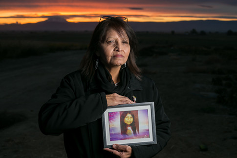 Trudi Lee Clark poses for a portrait Wednesday, Oct. 24, 2018, as she holds a framed photograph of her missing sister Janice Hannigan at the site of her family's previous home in Toppenish, Wash. Janice Marie Hannigan was 16 when she went missing in 1971 and Trudi never stopped looking for her. She posted flyers on various websites and social media pages and every time she finds herself in a crowd, scans faces to see if any women may be her sister.