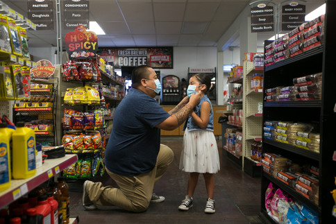 """Valient Clark, a videographer with the Yakama Nation's COVID-19 Project, adjusts 6-year-old Alaira Clark's mask Tuesday, July 21, 2020, at Kyle's Korner, 2421 W. Wapato Road in Wapato, Wash. Valient produced a short film featuring his 6-year-old daughter titled """"Kuthla."""" He created the video to share why it is important to wear a mask for the Yakama Nation's COVID-19 Project."""