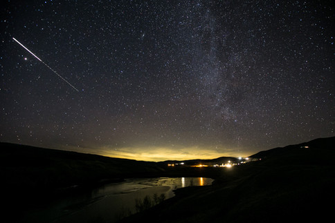 A faint yellow glow of light pollution from the greater Seattle area is seen looking northwest over Wenas Lake near Selah, Wash., on Wednesday, Dec. 9, 2020. The calm weather, orientation of the camera, and long exposure revealed the faint yellow glow as city lights, according to Zach Schierl, astronomy and physical science instructor at Yakima Valley College. Above the yellow glow, a vibrant Milky Way stretches over the landscape of Evans Canyon.