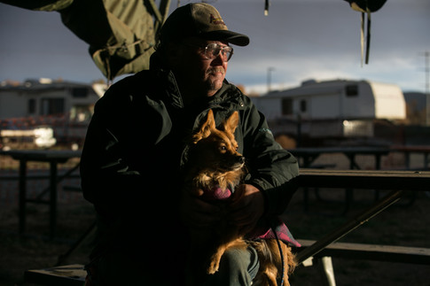"""Scruffy, a 4-year-old fox terrier, embraces Marine Corps veteran Richard Vaughn during an evening walk Tuesday, Nov. 10, 2020, on a trail near Camp Hope in Yakima, Wash. Vaughn, who struggles with PTSD, shared how he found healing through his canine companion. """"You get one like him only once in a lifetime,"""" Vaughn said."""