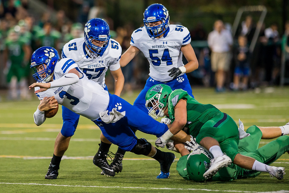 Bothell quarterback Jacob Sirmon attempts to run the ball against Woodinville during the Bothell vs. Woodinville KingCo 4A football game Friday.