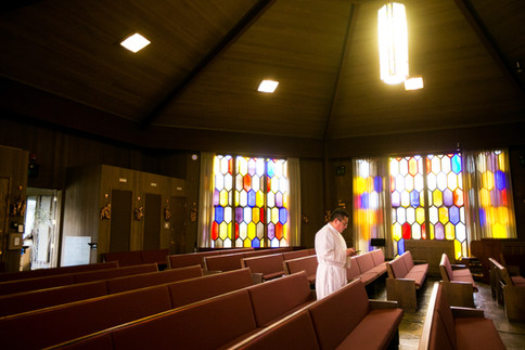 The Rev. César Vega stands in between empty pews during evening prayer Friday, March 27, 2020, at Holy Family Catholic Church in Yakima, Wash.