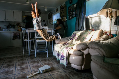 As Andrea Hernandez works on her computer at the dinner table, Diego Torres, 4, attempts to jump over his toy guitar at their home in Yakima, Wash., on Tuesday, Aug. 25, 2020. Hernandez, who works from home due to the coronavirus pandemic, will now tackle work tasks, helping her two eldest children with their homework and keeping their youngest son occupied.