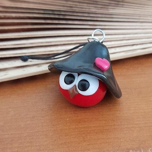 Grigri oiseau rouge avec un chapeau