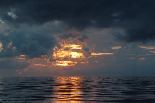 als de zon onder de donkere wolken zakt