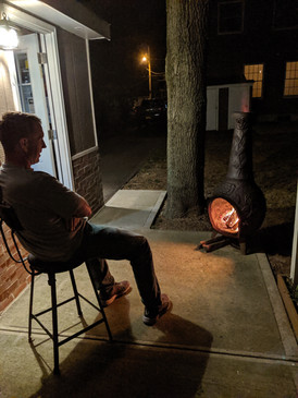 Devon sitting outside by the fire
