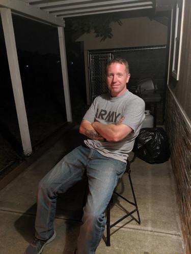 Devon sitting next to his garage