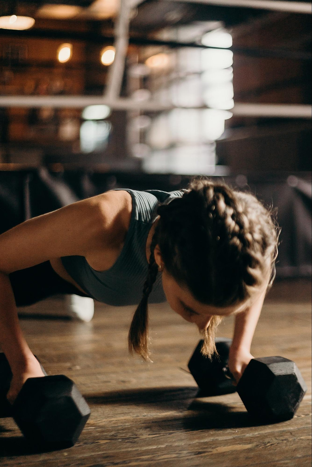 Woman doing a pushup with weights