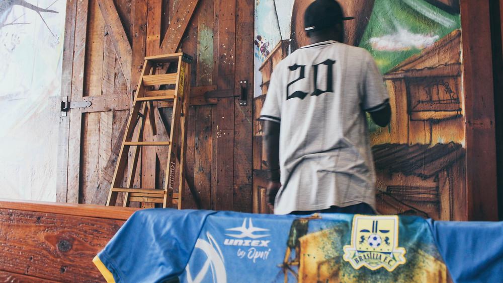 Toddy em ação na parede do bar Escala K-Town, camisa do Brasília FC da coleção UNIEX by OPNI exposta logo a frente.