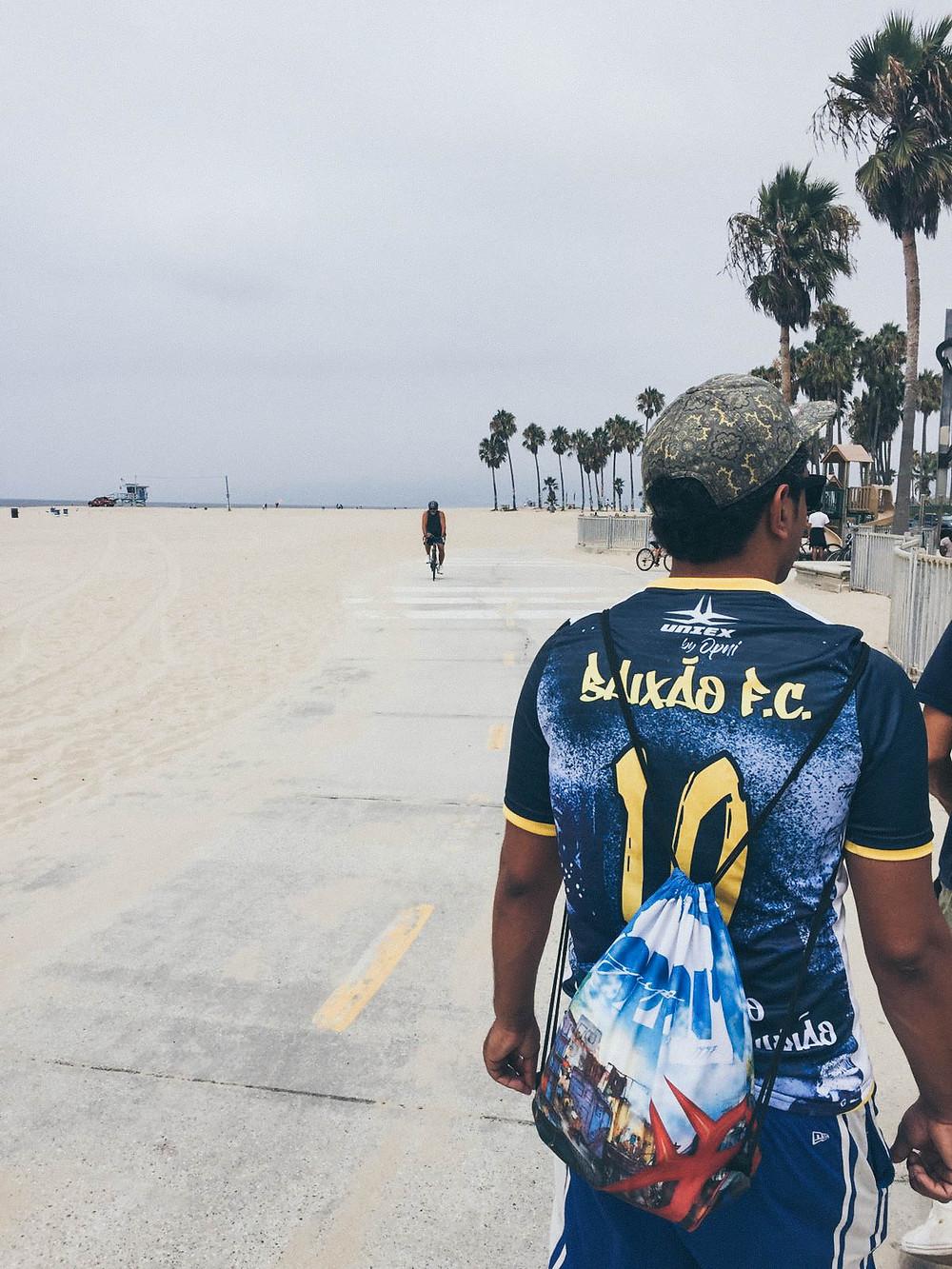 Val do grupo OPNI em Venice Beach usando a camisa do Baixão FC da coleção UNIEX by OPNI