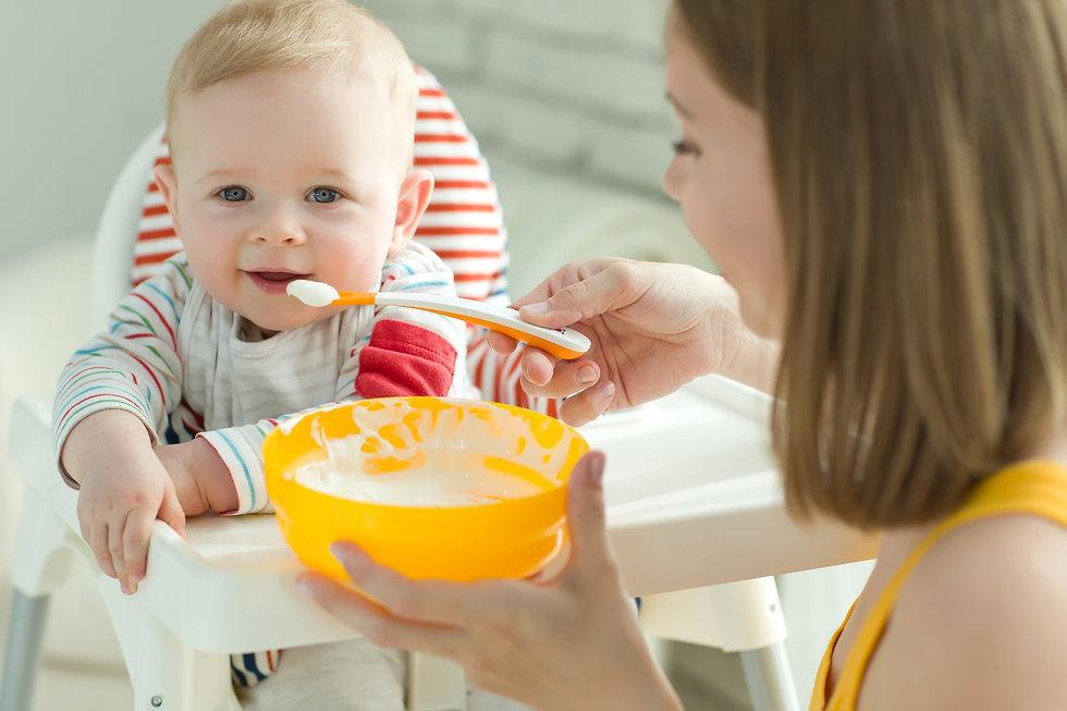 A woman is feeding a child .jpg
