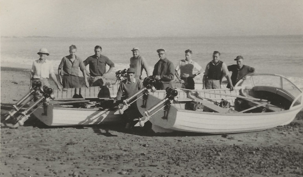 Two boats & their crews sitting on the beach pre-launch