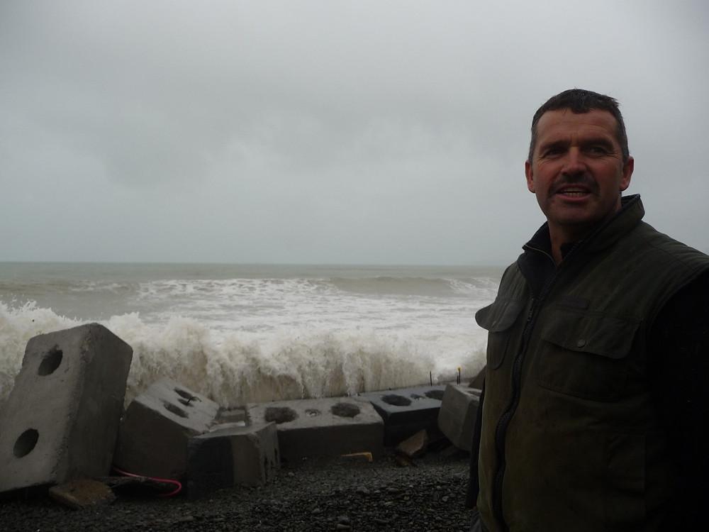 Mark Lawrence next to concrete block seawall, 23 Clifton Road, Haumoana