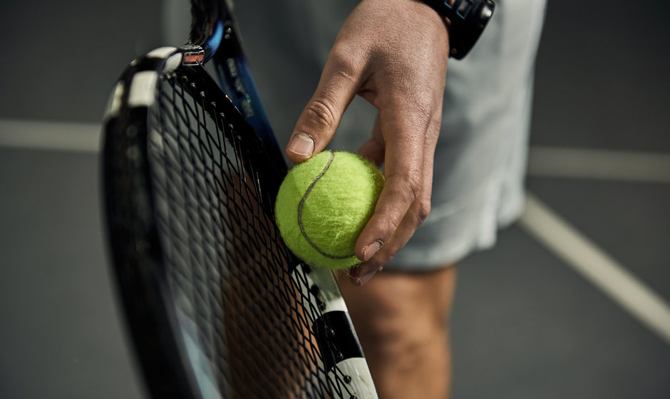 Close-up of male hand holding tennis bal