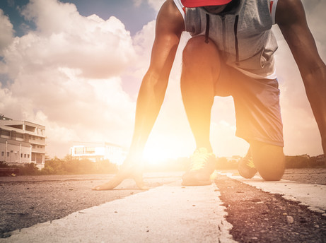 Athlete man in running pose on city stre