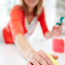 Woman Cleaning Surface In Kitchen_edited