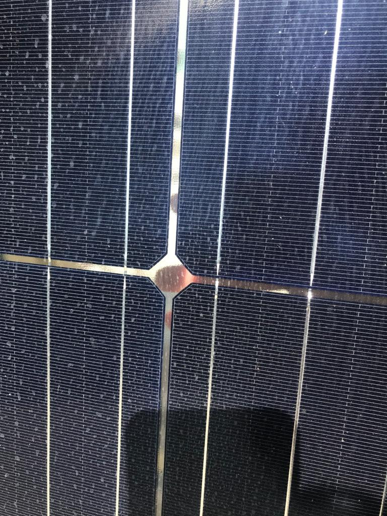 Bifacial solar panel is transparent, able to see fingers at the back.,
