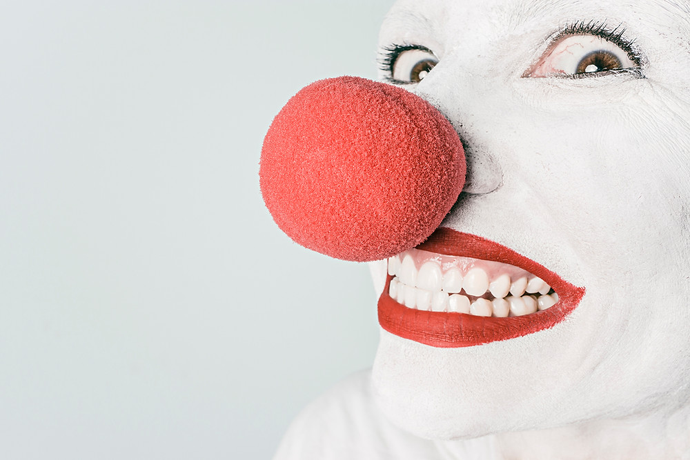 A creepy clown in white facepaint with a red nose glancing at the camera with a menacing grin