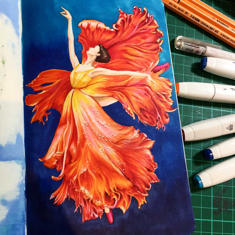 A ballerina dressed in orange tulip petals on a blue background drawn in a sketchbook and marker pens on a green gridded rubber pad
