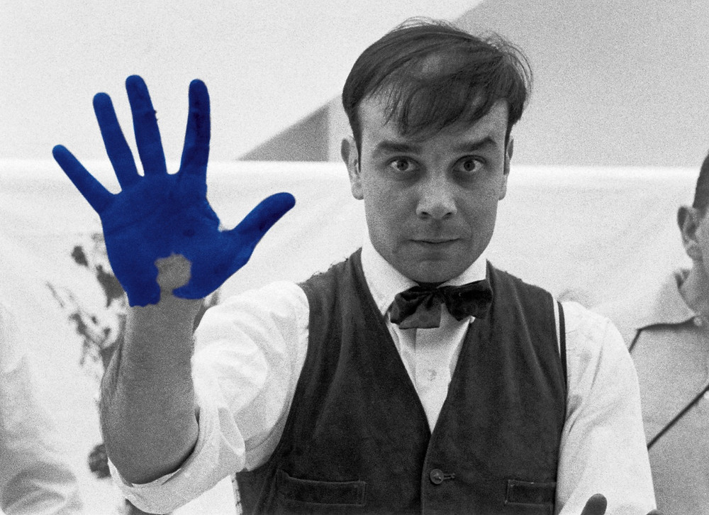 A man with one raised hand painted in blue
