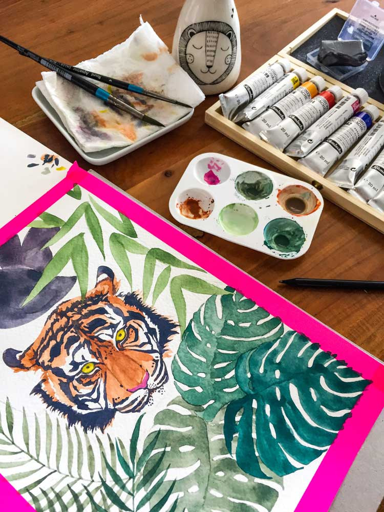 A desk with a watercolor painting of a tiger, Schmincke gouache paints, brushes and a mixing plate