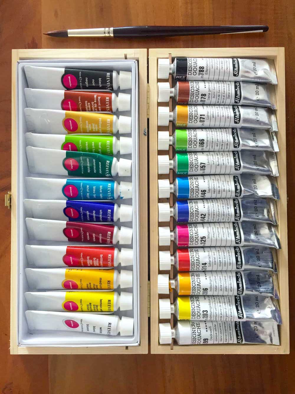 Two sets of 12- tube paints lined up in their boxes on a wooden table and a brush on the right side