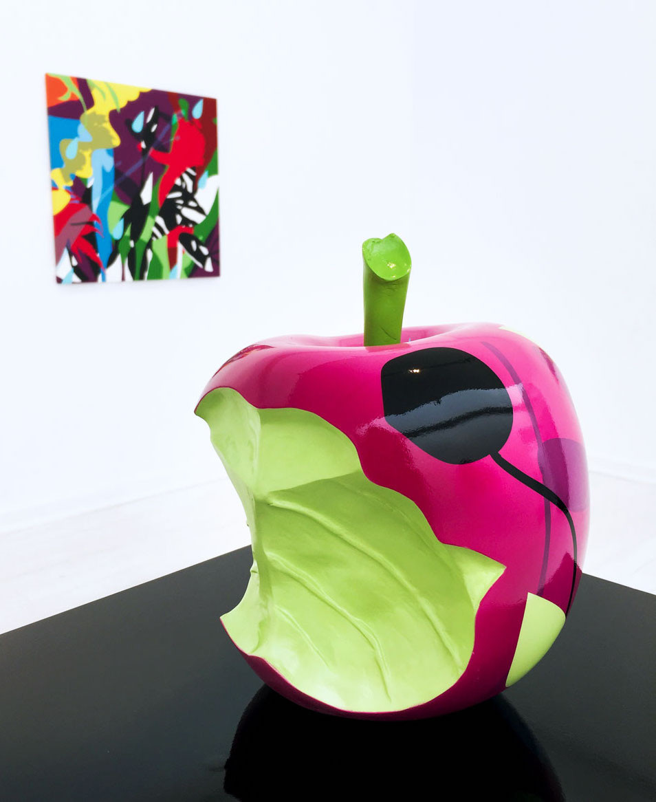 A bitten painted pink apple sculpture placed on a black surface and set against a white background with a canvas painting hanging on the wall