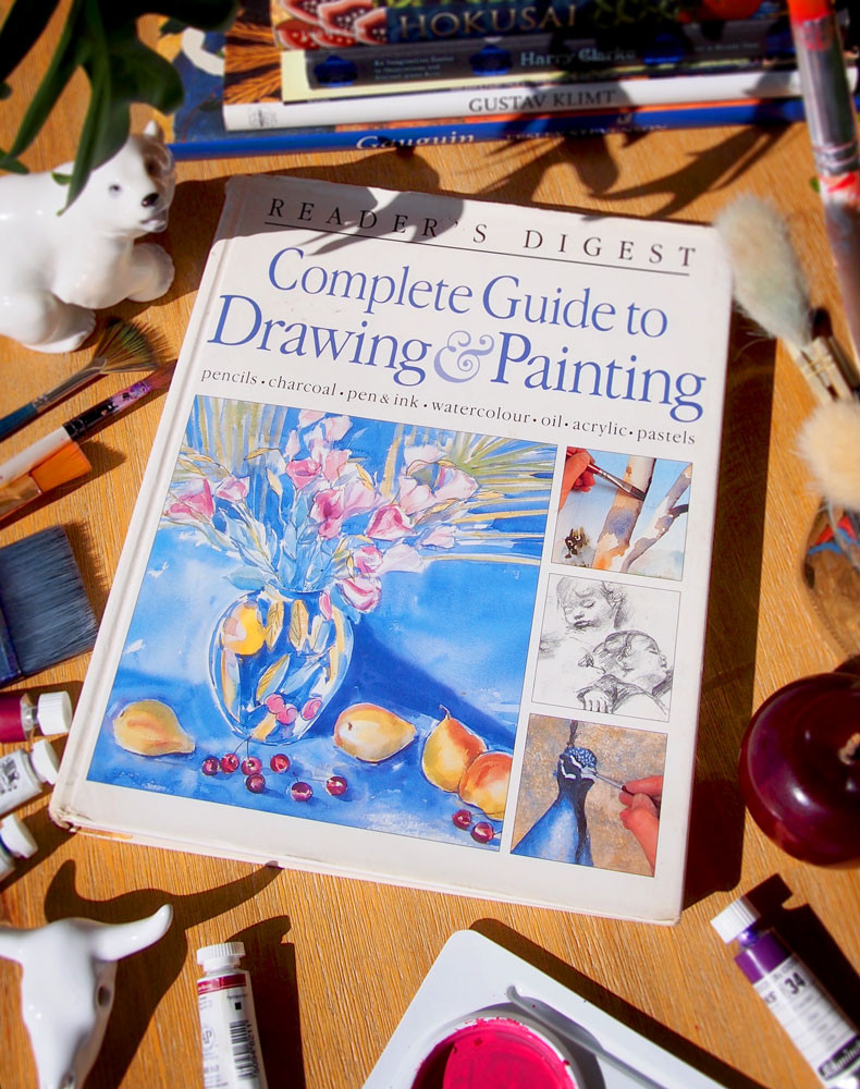 A Reader's Digest art book about drawing and painting laid on a wooden table and surrounded by books, polar bear figurine, brushes, paints, a wooden apple and a mixing plate