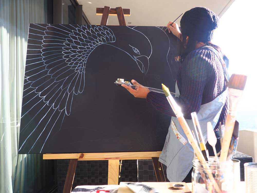 Michelle Carlos painting a bird on a black canvas