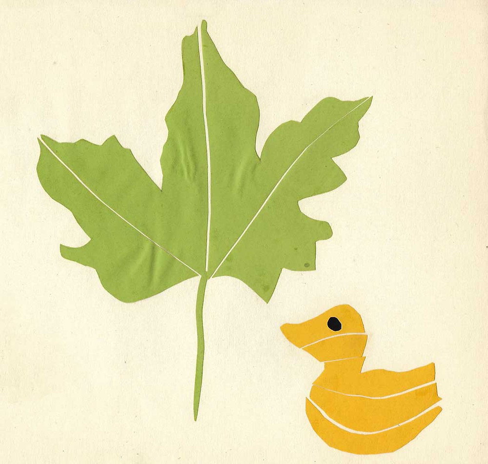 Paper cutout of a green maple leaf and a yellow duckling