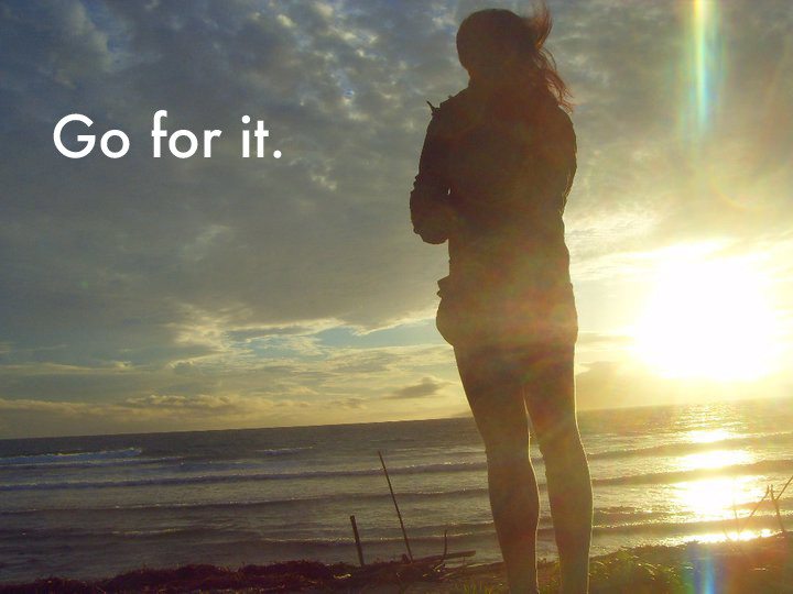 A silhouette of a girl standing at a beach looking at the sunrise. The text on the top left reads, Go for it.