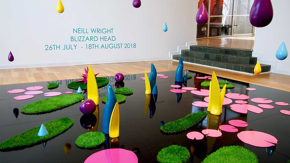 "A colorful installation of painted wood carvings and figures laid out on a black reflective surface resembling a pond with pink lily pads, green grass patches, purple apples and hanging candy-colored raindrops. A backdrop reads ""Neill Wright Blizzard Head 26th July - 18th August 2018"""