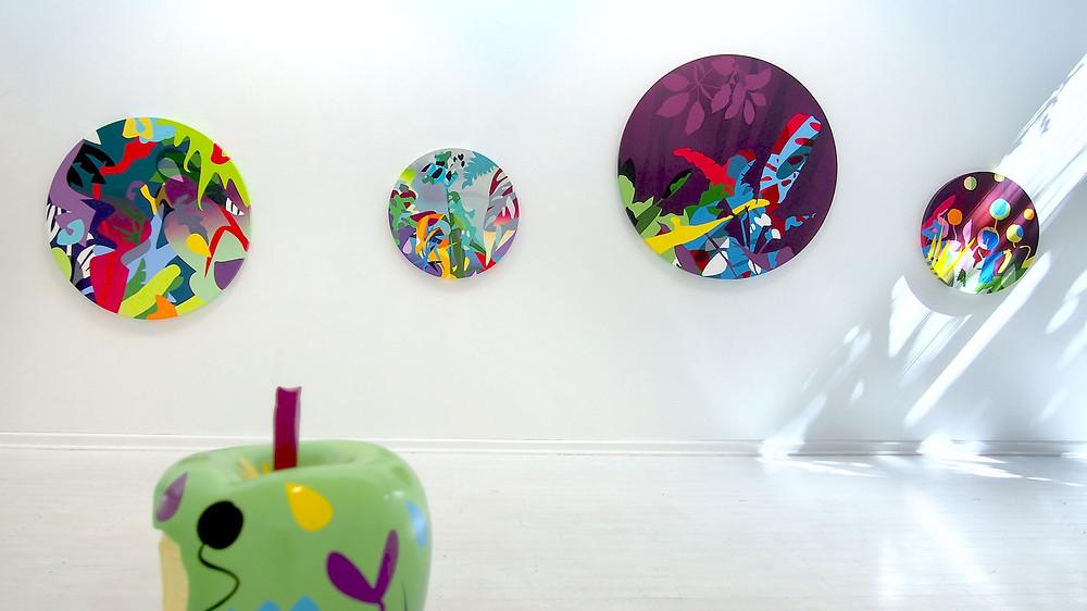 A line up of circular colorful paintings of Neill Wright hanging on a white wall and a painted green apple sculpture in the foreground