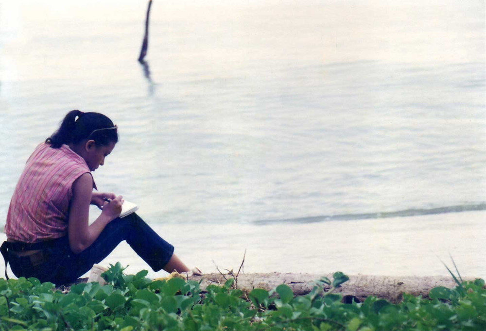 Michelle Carlos sketches by a lake during a film shoot