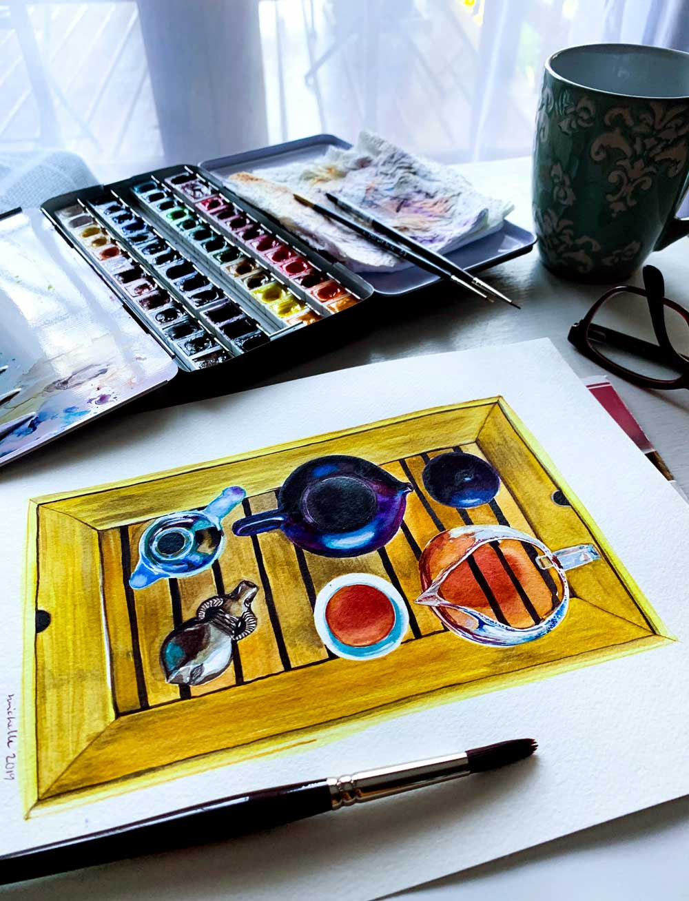 Watercolor paints and a painting of gongfu cha on a table