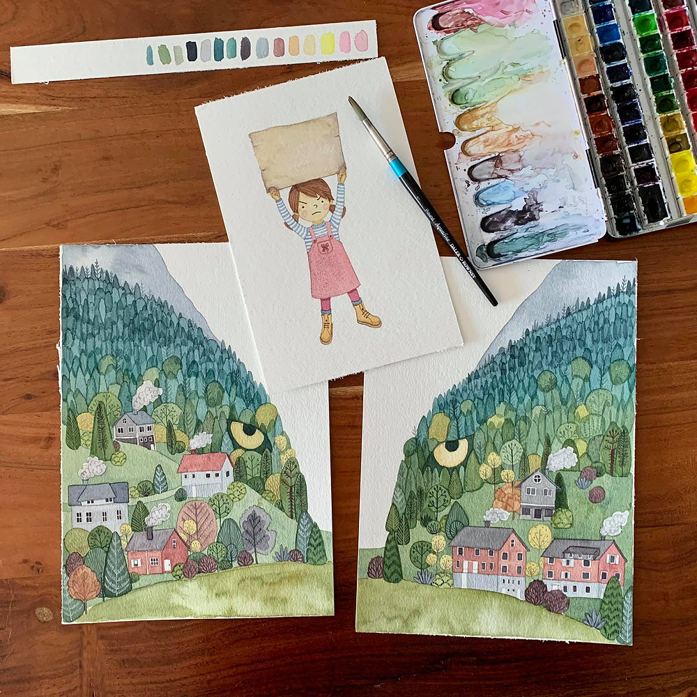 Watercolor landscape illustrations and watercolor paints on a wooden table
